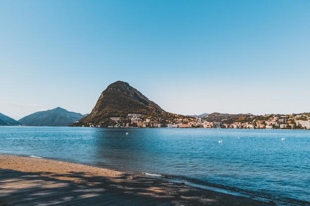 Horizontale opname van de prachtige blauwe zee, omringd door rotsachtige bergen en betonnen gebouwen