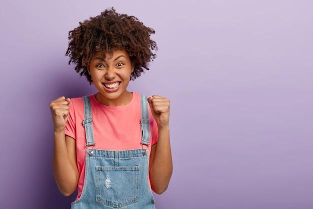 Horizontale opname van dolblij zwarte afro-vrouw balde vuisten met triomf, viert succes, drukt goede emoties uit, gekleed in vrijetijdskleding, poseert over paarse muur, wacht op aankondiging van resultaten