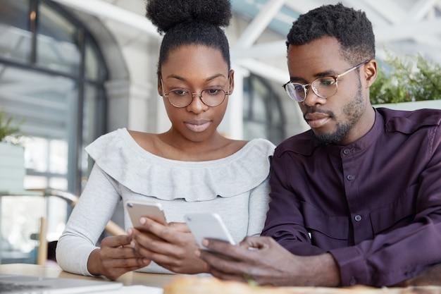 Horizontale opname van donkere jonge vrouwelijke en mannelijke freelancers typen tekstmeldingen op smartphones, online chatten