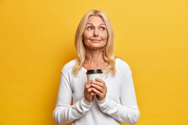 Horizontale opname van dromerige, bedachtzame oma die koffiepauze heeft, geniet van vrije tijd, herinnert aan aangename herinneringen uit haar jeugd poses met een kopje warme drank nonchalant gekleed