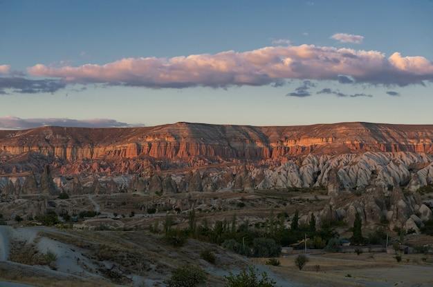 Horizontale opname van een canyon met weinig planten aan de voet en enkele wolken aan de hemel