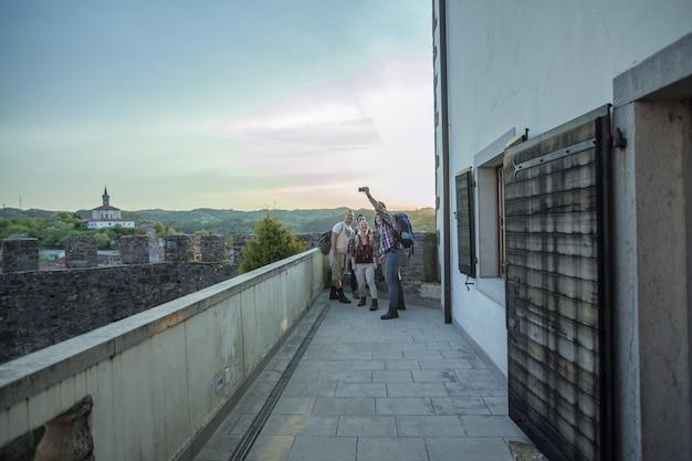 Horizontale opname van een groep vrienden die foto's maken en genieten van hun tijd op het balkon