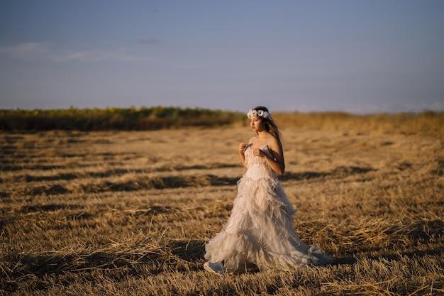 Horizontale opname van een jonge blanke vrouw in een witte jurk poseren in een veld