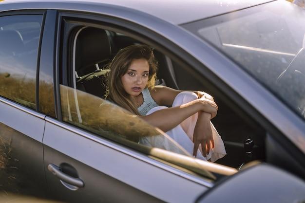 Horizontale opname van een mooie jonge blanke vrouw poseren in de voorstoel van een auto in een veld