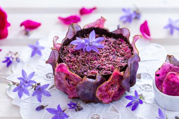 Horizontale opname van een peren rauwe veganistische paarse cake met gedehydrateerde peren op een wit tafelblad - veganistisch
