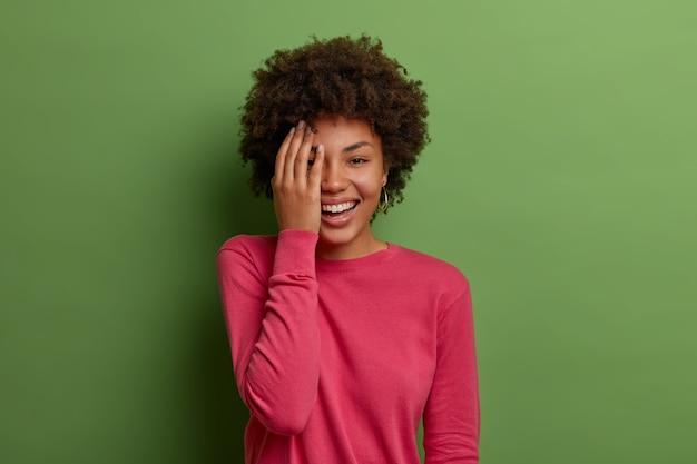 Horizontale opname van een positieve donkere vrouw maakt gezicht palm, grinnikt en bedekt de helft van het gezicht, drukt vreugde uit, draagt een roze trui, vormt tegen een groene muur. positieve emoties concept.
