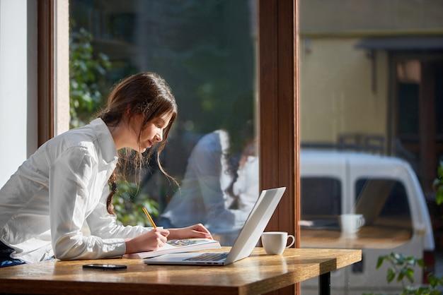 Horizontale opname van een prachtige jonge vrouwelijke student studyiong in het café bezig met haar laptop copyspace technologie communicatie mensen opstarten project brainstormen educatieve vrijetijdsbesteding.