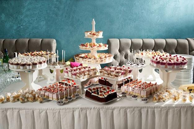Horizontale opname van een snoepbuffet aan de tafel van het restaurant vol met heerlijke desserts, taarten, cheesecakes, romige zoetigheden, feestelijke bijeenkomst, café, zoetwaren.