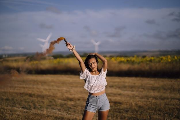 Horizontale opname van een vrouw poseren met een rookbom op een achtergrond van velden en windmolens