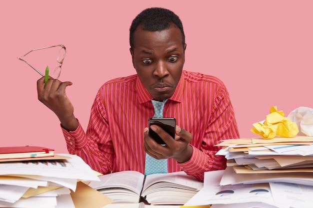 Horizontale opname van emotionele, verbaasde, verbaasde, donkere mannelijke werknemer houdt mobiele telefoon vast, staart naar het scherm en ontvangt bericht voor het betalen van rekeningen
