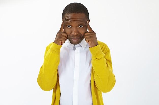 Horizontale opname van gefrustreerde ongelukkige jonge afro-amerikaanse man die lijdt aan ernstige hoofdpijn, vingers tegen tempels drukt, ze masseert om pijn te verlichten, hulpeloze gezichtsuitdrukking heeft