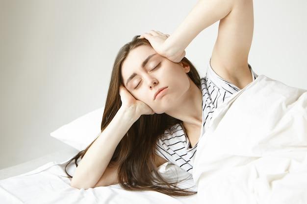 Horizontale opname van gefrustreerde, slaperige jonge vrouw die gestrest is na een feestje op de late avond, hoofd knijpt vanwege migraine, zich slaperig en onwel voelt, in bed blijft in plaats van naar haar werk te gaan