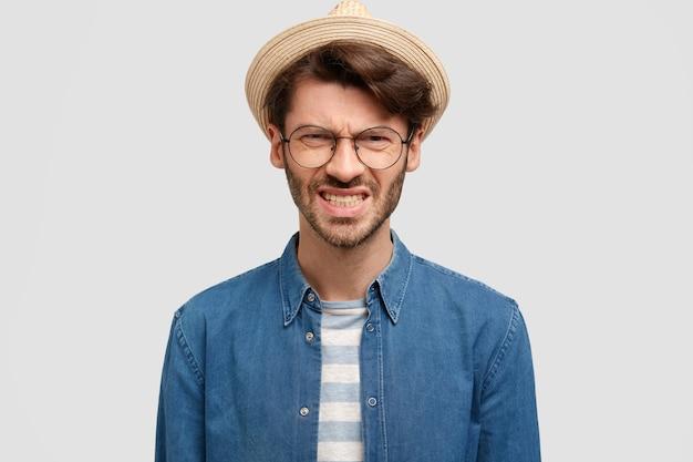Horizontale opname van geïrriteerde ongeschoren man klemt zijn tanden, fronst zijn wenkbrauwen, draagt een strohoed en een spijkerblouse, voelt ergernis