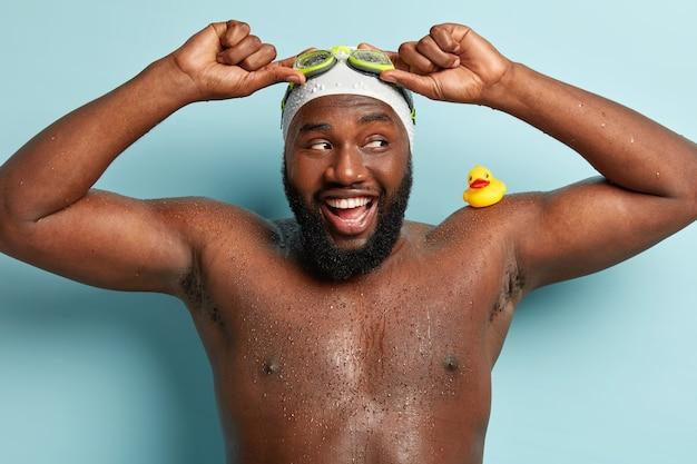 Horizontale opname van gelukkig afro-amerikaanse man in hoge geest, past bril om te zwemmen