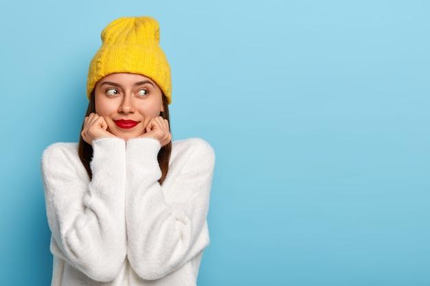 Horizontale opname van gelukkig dromerige europese vrouw draagt minimale make-up, rode lippenstift, kijkt opzij, gekleed in gele hoed en witte trui, vormt tegen een blauwe achtergrond, gefascineerd en tevreden