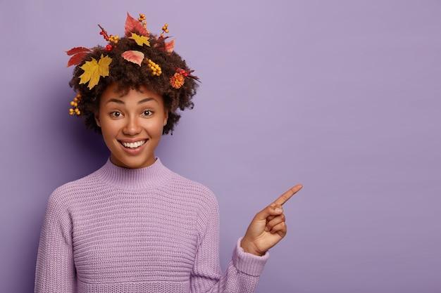 Horizontale opname van gelukkige vrouw helpt bij het ophalen van de beste keuze, wijst met de wijsvinger op lege ruimte, lacht aangenaam, draagt warme trui, heeft krullend kapsel met herfstbladeren