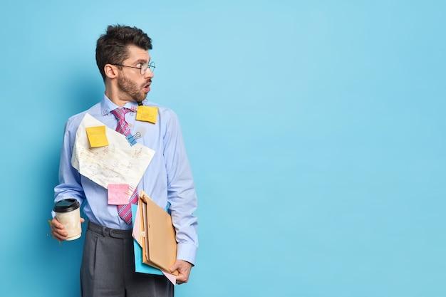 Horizontale opname van geschokte mannelijke beheerder kijkt opzij met angstige uitdrukking kan niet geloven dat zijn ogen een formeel overhemd en een broek dragen, drinken afhaalmaaltijden koffie draagt documenten in mappen