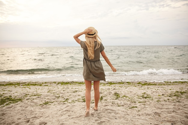 Horizontale opname van jonge langharige witharige dame die haar boothoed met opgeheven hand houdt terwijl ze naar zee kijkt en met haar rug over de kust staat