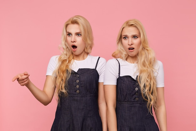 Horizontale opname van jonge verbijsterde langharige witharige vrouwtjes die hun mond openhouden terwijl ze verward opzij kijken, geïsoleerd op roze achtergrond