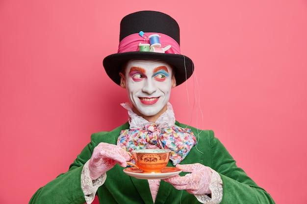 Horizontale opname van lachende vrolijke mysterieuze hoedenmaker besteedt vrije tijd op theekransje draagt hoed en kostuum met vlinderdas heeft vakantiestemming poses tegen roze muur