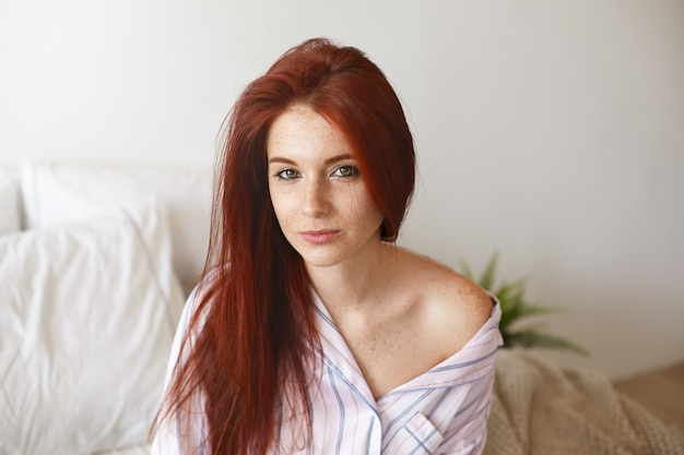 Horizontale opname van mooie jonge vrouw met rood haar en sproeten zittend op wit beddengoed met slaperige blik omdat ze 's nachts niet genoeg slaap had. ochtend-, beddengoed- en lifestyle-concept