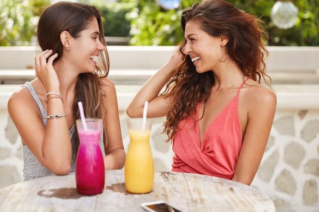 Horizontale opname van mooie vrouwen met luxe haar, elkaar positief aankijken, cocktails drinken, recreatietijd doorbrengen in een restaurant