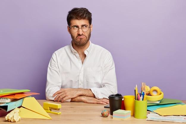 Horizontale opname van ontevreden man grijnst gezicht, kijkt opzij, elegant gekleed, draagt een bril voor zichtcorrectie, zit op de werkplek, werkt lang aan projectwerk