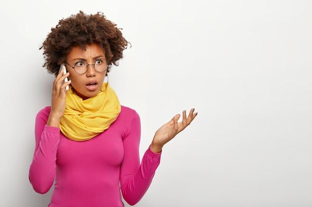 Horizontale opname van ontevreden vrouw met donkere huid verhoogt palm heeft verbaasde uitdrukking, negatief gesprek via mobiel, gekleed in levendige kleding en transparante bril