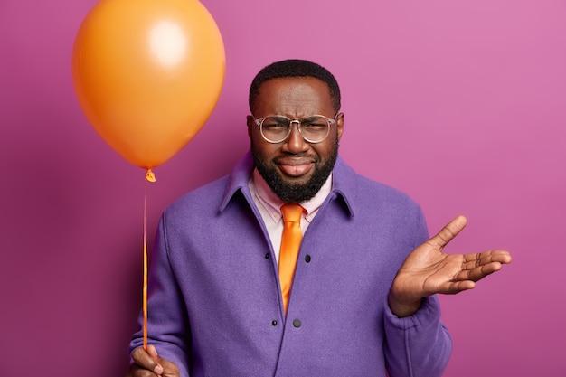 Horizontale opname van ontevreden zwarte volwassen man gebaren met teleurstelling, fronst gezicht, houdt ballon vast, kan niet beslissen wat te doen tijdens vakantie