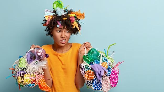 Horizontale opname van ontevredenheid afro-amerikaanse vrouw met donkere huid fronst gezicht als vuilnis oppikt, de omgeving reinigt, netzakken met plastic dingen vasthoudt, wegkijkt, vraagt om geen afval op de natuur te gooien