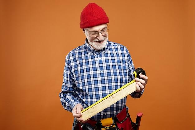 Horizontale opname van positief geschoolde oudere europese vakman die pveralls en brillen draagt die een toekomstige houten meubel vasthoudt, de maat meet en glimlacht, genietend van handmatig werk