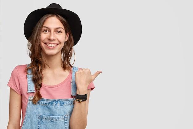 Horizontale opname van positieve vrouwelijke eigenaar van de boerderij geeft aan bij haar eigendom, toont tuin met rijke oogst, heeft gelukkige uitdrukking, draagt elegante zwarte hoed, geïsoleerd op een witte muur met lege ruimte