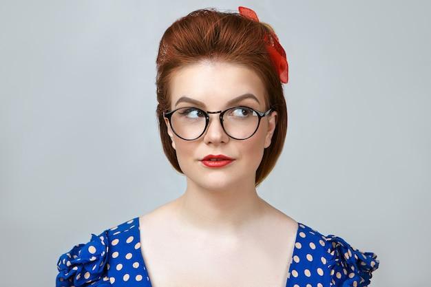 Horizontale opname van prachtige stijlvolle 25-jarige huisvrouw met doordachte uitdrukking