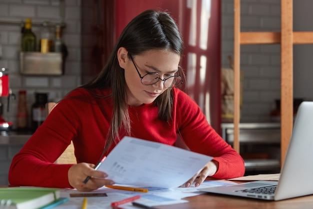 Horizontale opname van projectmanager in bril en rode jumper, kijkt aandachtig naar documenten, denkt na hoe klanten aantrekken en inkomen verhogen, poseert tegen keukeninterieur met draagbare laptop