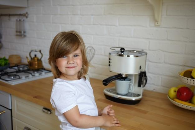 Horizontale opname van schattige zorgeloze vrouwelijke jongen van voorschoolse leeftijd dragen witte t-shirt met gelukkige blik, staande aan de keukentafel, koffie maken voor haar vader. zorgeloos kinder- en kookconcept