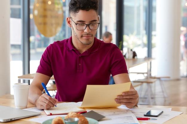 Horizontale opname van serieuze bankier houdt papier vast, schrijft creatieve ideeën voor de ontwikkeling van succesvol bankbedrijf, houdt pen vast om in kladblok te schrijven, omringd met moderne gadgets in cafetaria