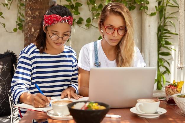 Horizontale opname van serieuze dames kijken samen naar webinar, verbonden met wifi in cafetaria