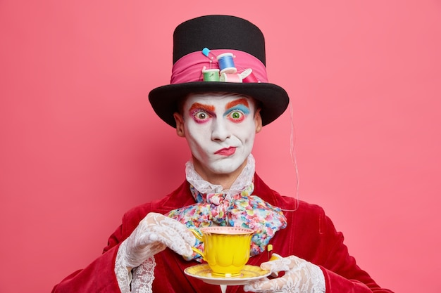 Horizontale opname van serieuze mannelijke hoedenmaker poses met kopje thee draagt hoed heeft manieren van aristocratische herenjurken voor maskerade carnaval vormt binnen