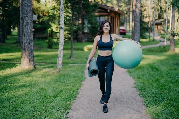 Horizontale opname van sportvrouw draagt bijgesneden top en beenkappen, draagt fitnessbal en opgerolde karemat, loopt op de weg rond bomen en groen gras, leidt een gezonde levensstijl.