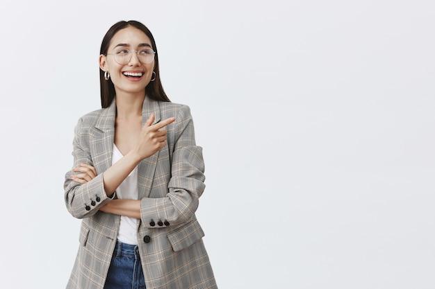 Horizontale opname van stijlvolle vrouwelijke vrouw in glazen en trendy oorbellen, lachend van plezier en geluk terwijl ze kijkt en wijst naar de rechterbovenhoek, geamuseerd over grijze muur