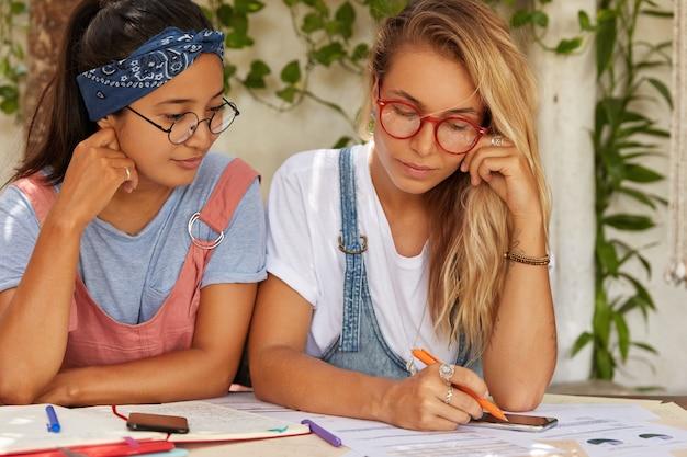 Horizontale opname van studenten of collega's die een gesprek voeren over een gemeenschappelijk project, naar papieren kijken, wat aantekeningen maken in notitieblok, pen vasthouden