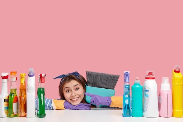 Horizontale opname van tevreden huishoudster draagt hoofdband, wijst naar wasmiddelen, draagt de bezem dichtbij, houdt van het perfecte effect
