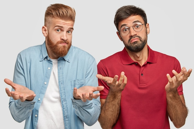 Horizontale opname van twee bebaarde jongens die geen idee hebben van aarzelende gezichtsuitdrukkingen, met hun handpalmen in verbijstering gespreid