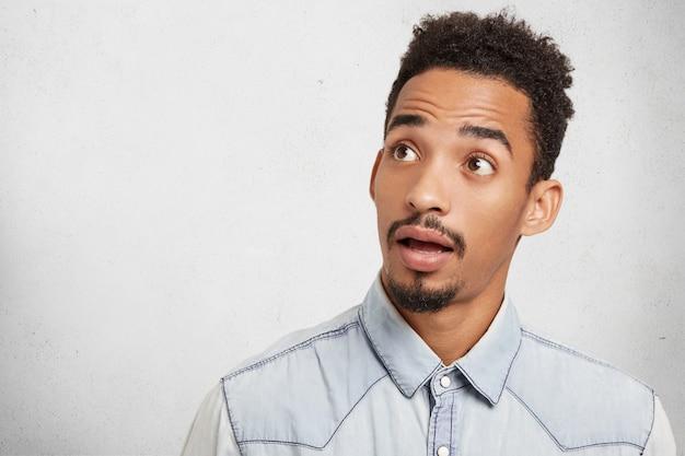 Horizontale opname van verbaasde hipster man met trendy kapsel, bruine ogen, baard en snor ziet er verrassend opzij uit,