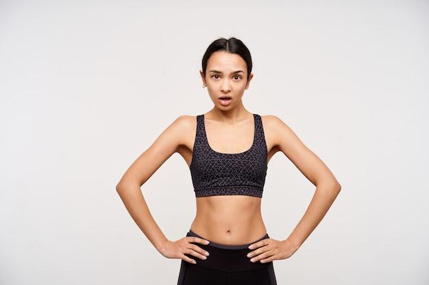 Horizontale opname van verbaasde jonge bruinogige brunette sportieve vrouw die verward naar de voorkant kijkt terwijl ze over een witte muur staat met de handen op haar middel