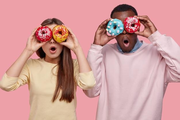 Horizontale opname van verrast donkere man bedekt ogen met heerlijke sprankelende donuts, staat in de buurt van haar vriendin, samen vrije tijd doorbrengen