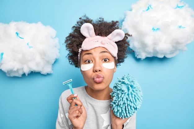 Horizontale opname van verrast vrouw houdt lippen gevouwen stuurt airkiss op camera draagt slaapmasker comfortabele pyjama houdt scheermes bad spons geïsoleerd over blauwe muur