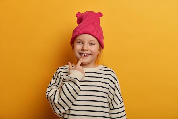 Horizontale opname van vrij klein vrouwelijk kind geeft aan op haar nieuwe tand, geeft om tanden, draagt stijlvolle kleding, heeft een grappige uitdrukking, grinnikt binnen, geïsoleerd over felgele muur