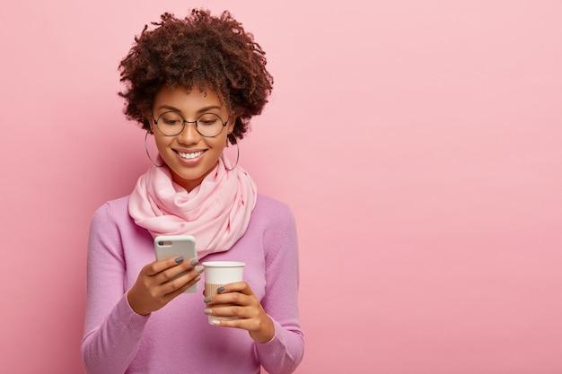 Horizontale opname van vrolijke donkere huid meisje stuurt tekstberichten, geniet van vrije tijd en aromatische drank, draagt paarse coltrui, geïsoleerd op roze achtergrond, lege ruimte gebied