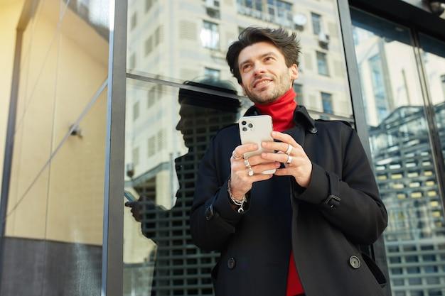 Horizontale opname van vrolijke jonge knappe donkerharige ongeschoren man die graag vooruit kijkt terwijl hij smartphone in opgeheven handen houdt, geïsoleerd op de achtergrond van de stad